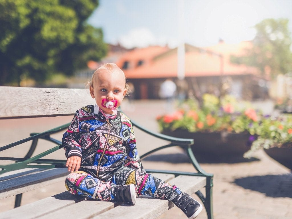 Toddler with pacifier sitting on a bench in the park