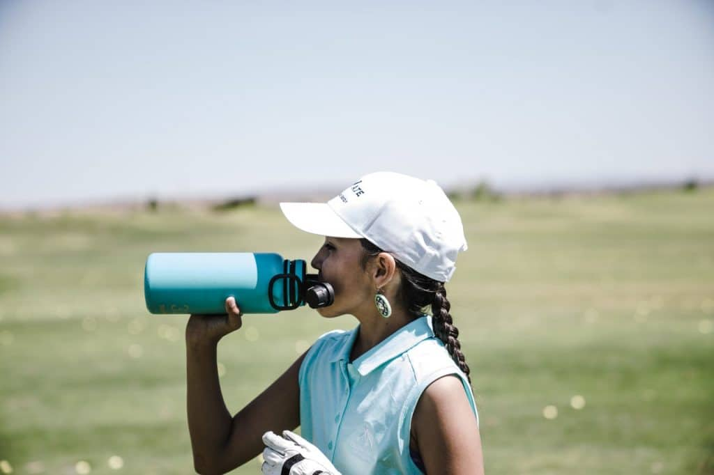 a girl drinking water from the best water bottle for kids