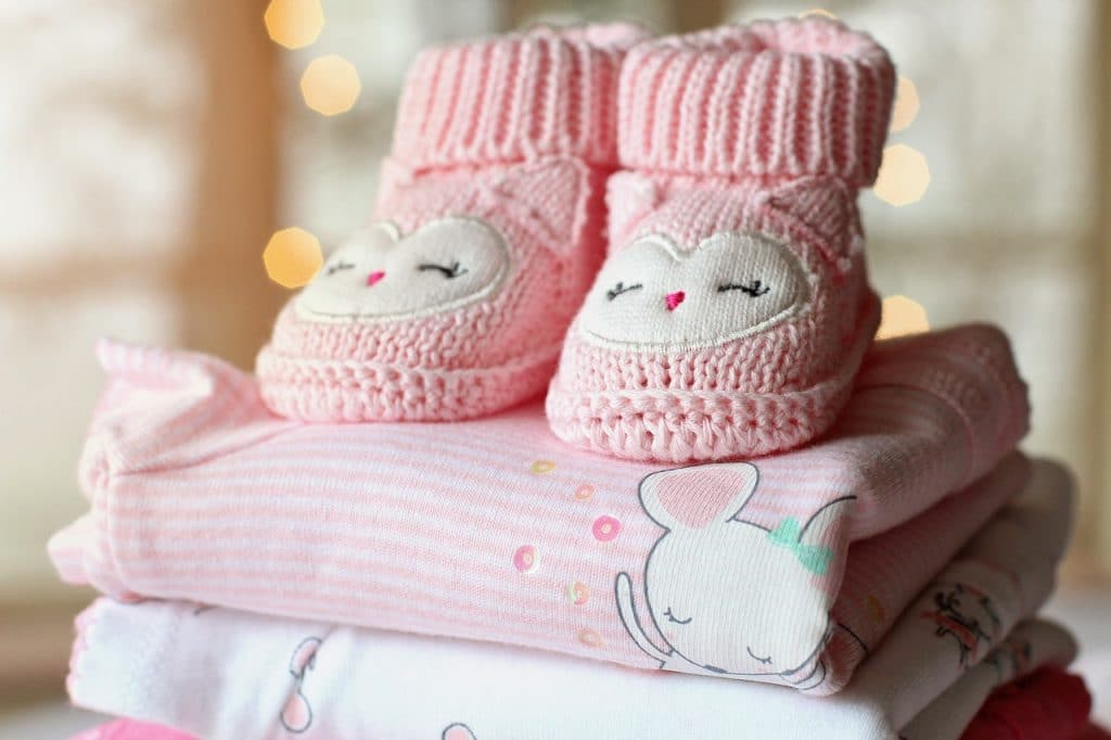 pink baby shoes on top of the blanket