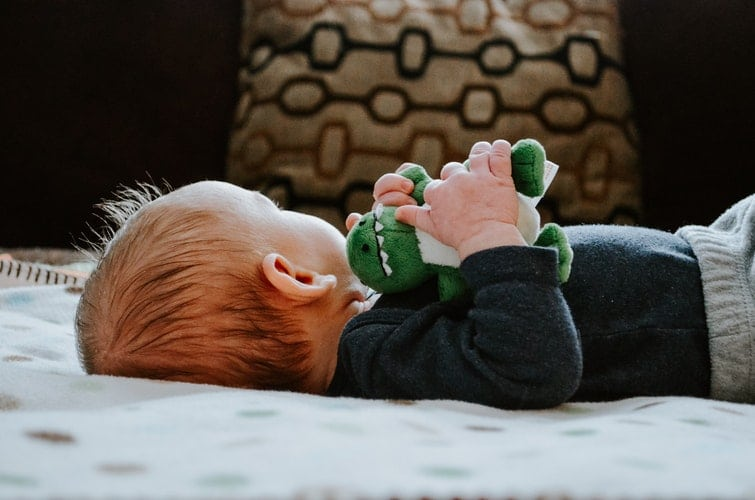 baby lying on white bed holding stuff toy