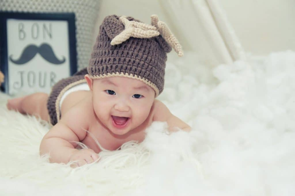 baby smiling on bed