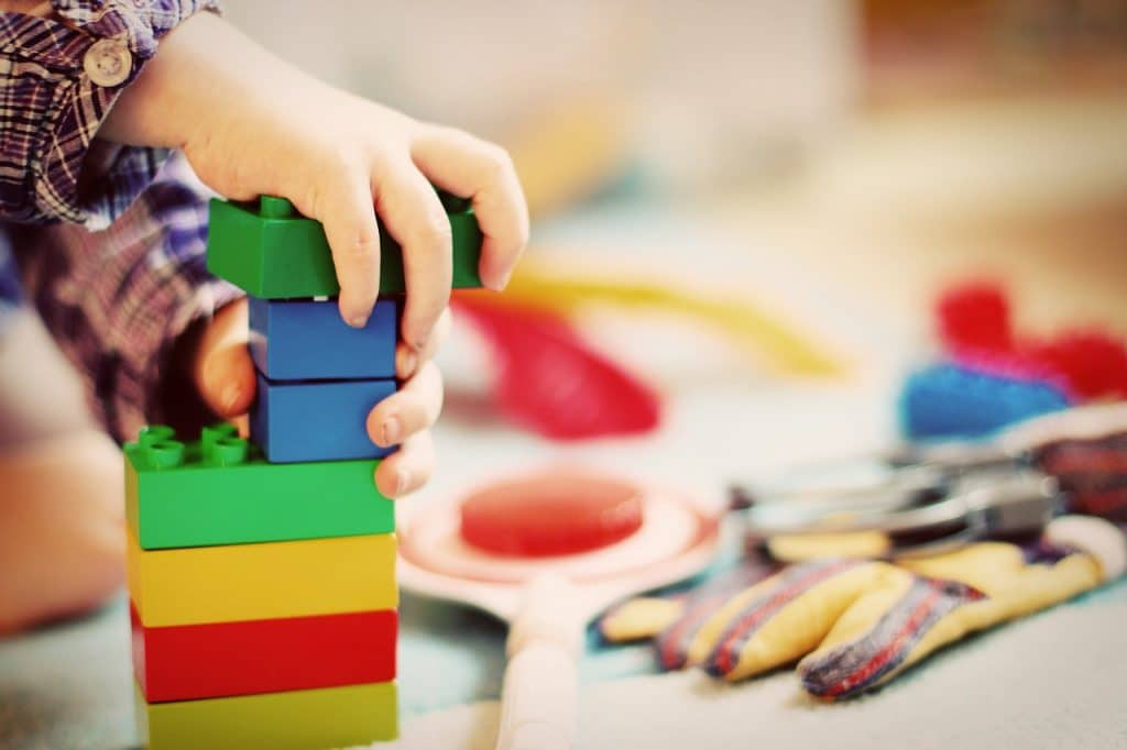 Different colors of blocks play by a toddler