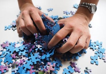 Hand squeezing a jigsaw puzzle
