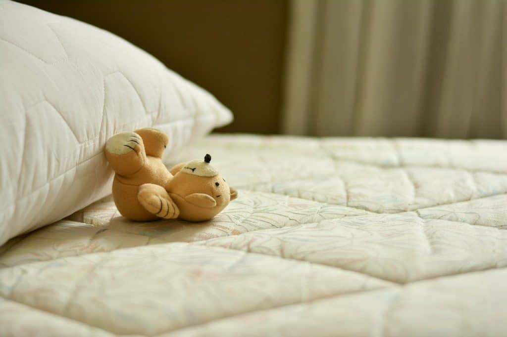 Teddy bear on a bare mattress waiting to be made, showing a pillow and