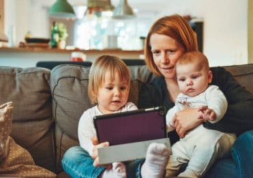mother viewing on the tablet with her two kids