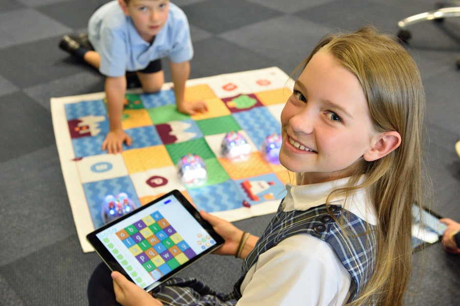Image of a girl holding a tablet while the boy lying on the carpet of pictures