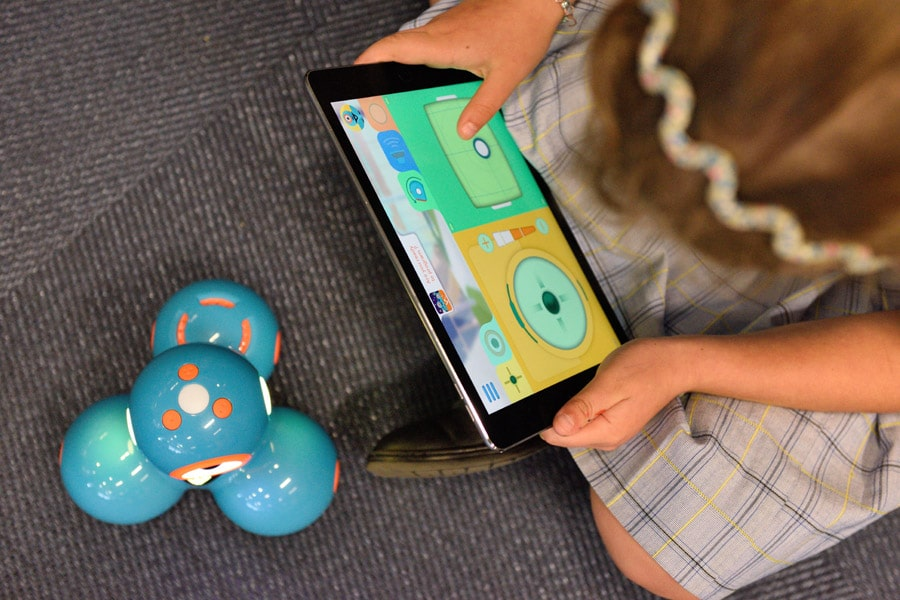 A toddler sitting down playing tablet and the best educational toys