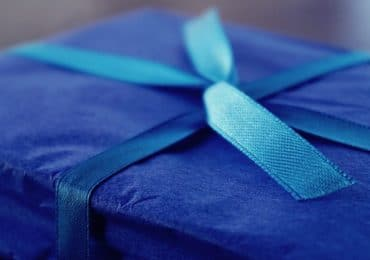 box wrapped in blue paper with blue ribbon