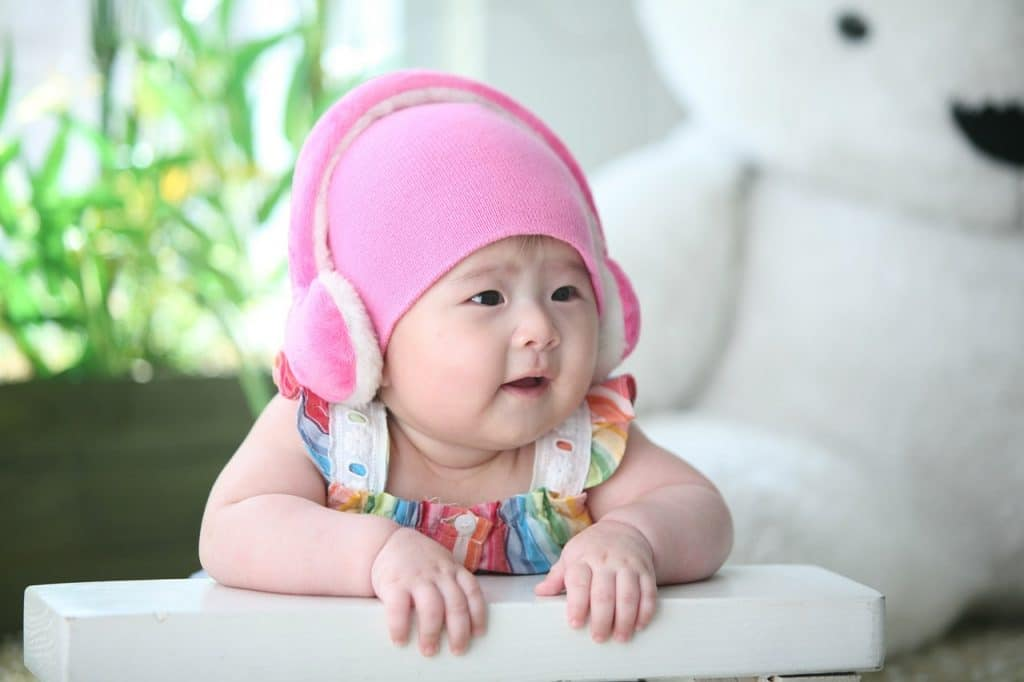 baby girl wearing pink earmuffs