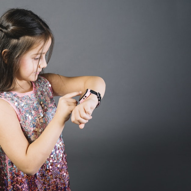 little girl watching time on wristwatch