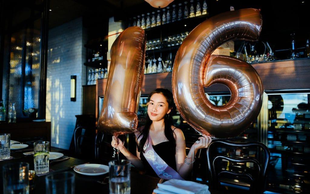 girl holding 16 balloons