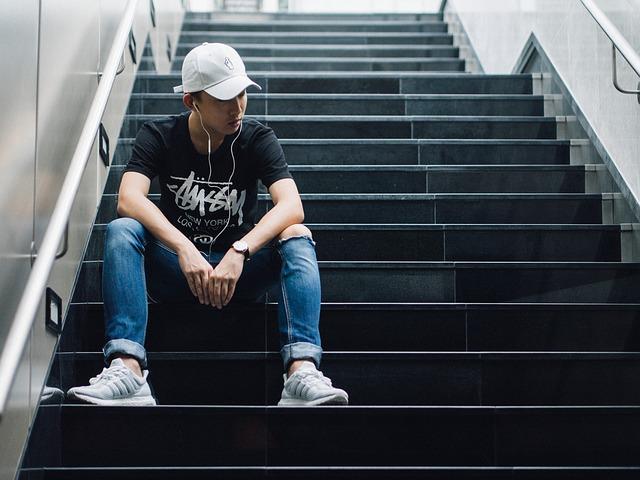 man hearing music in stairway