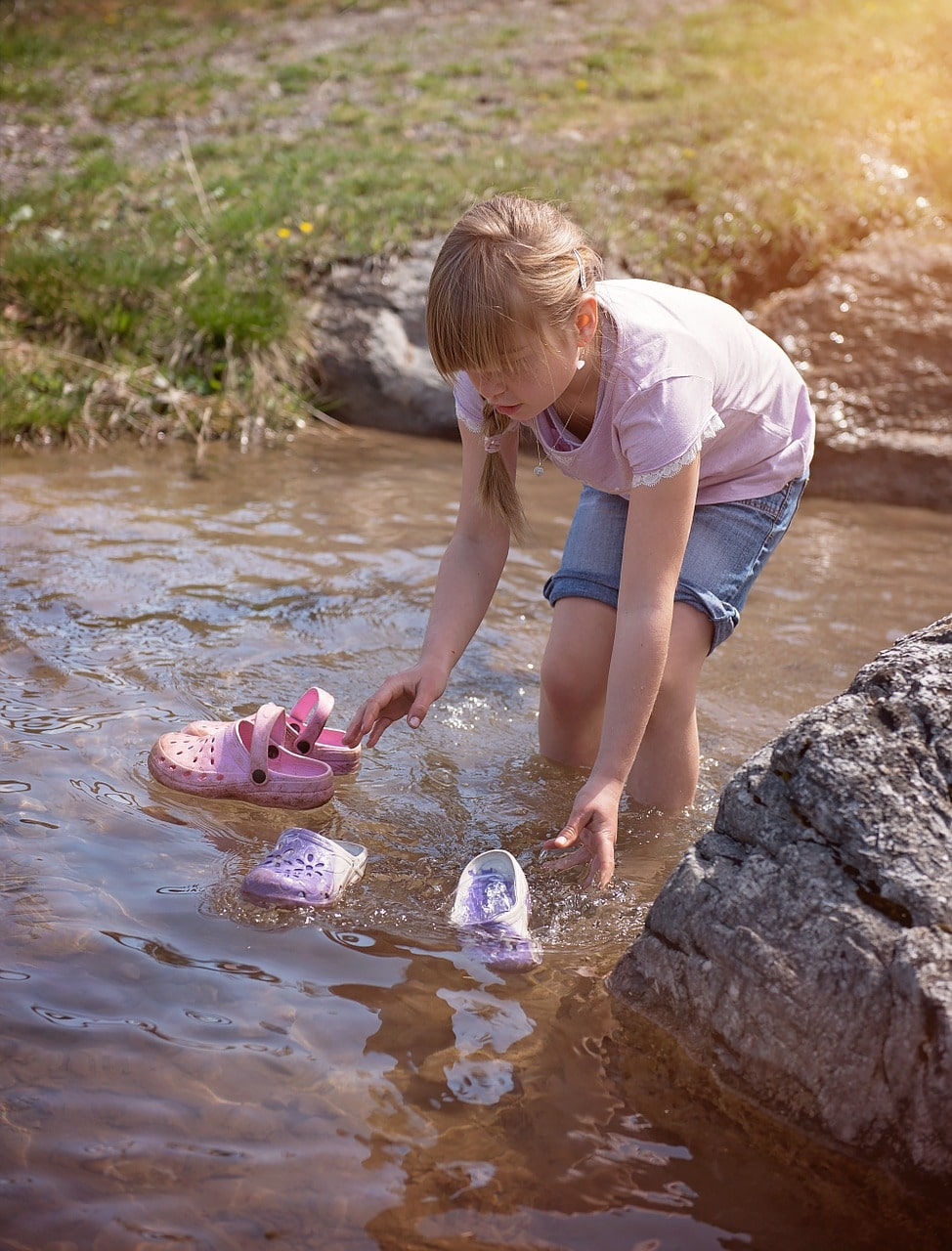 young girl washing shoes in the river