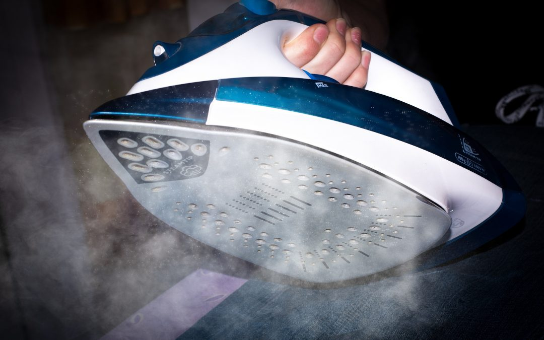 A woman's hand holds one of the best steam irons
