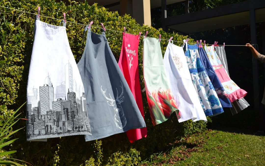 A row of the best kitchen aprons hanging on a line to dry outside.