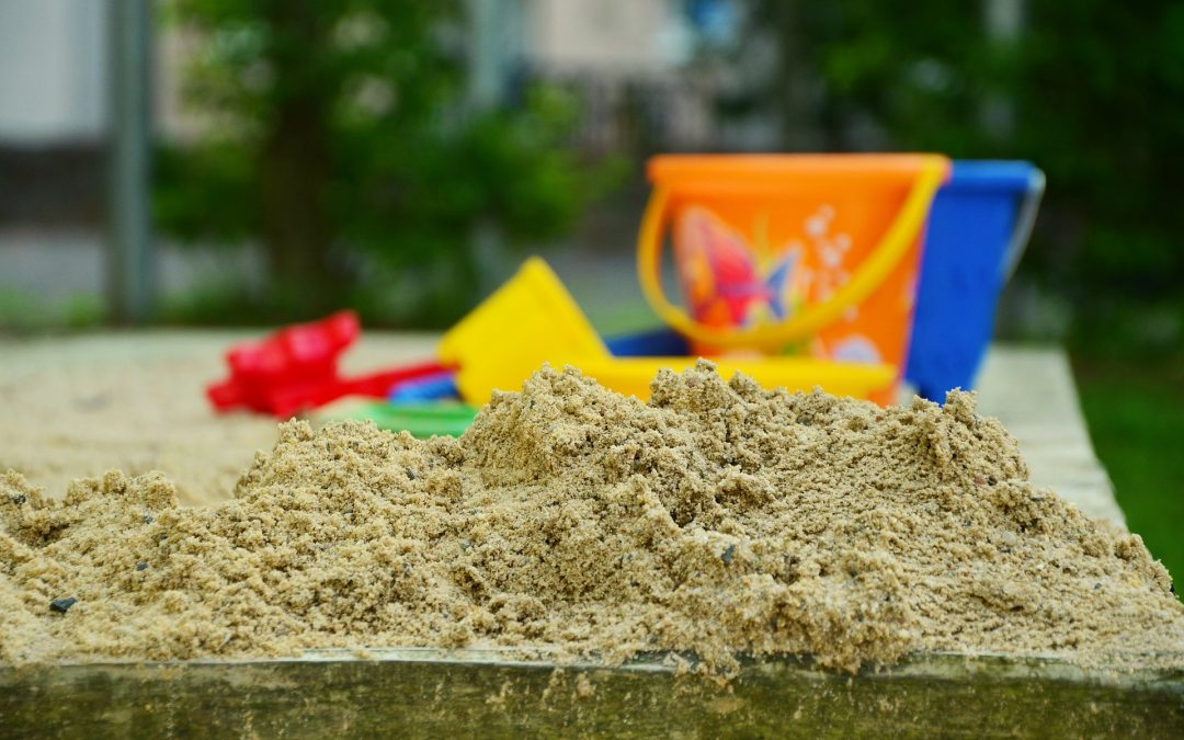 Sand and toys sitting on the water table for kids
