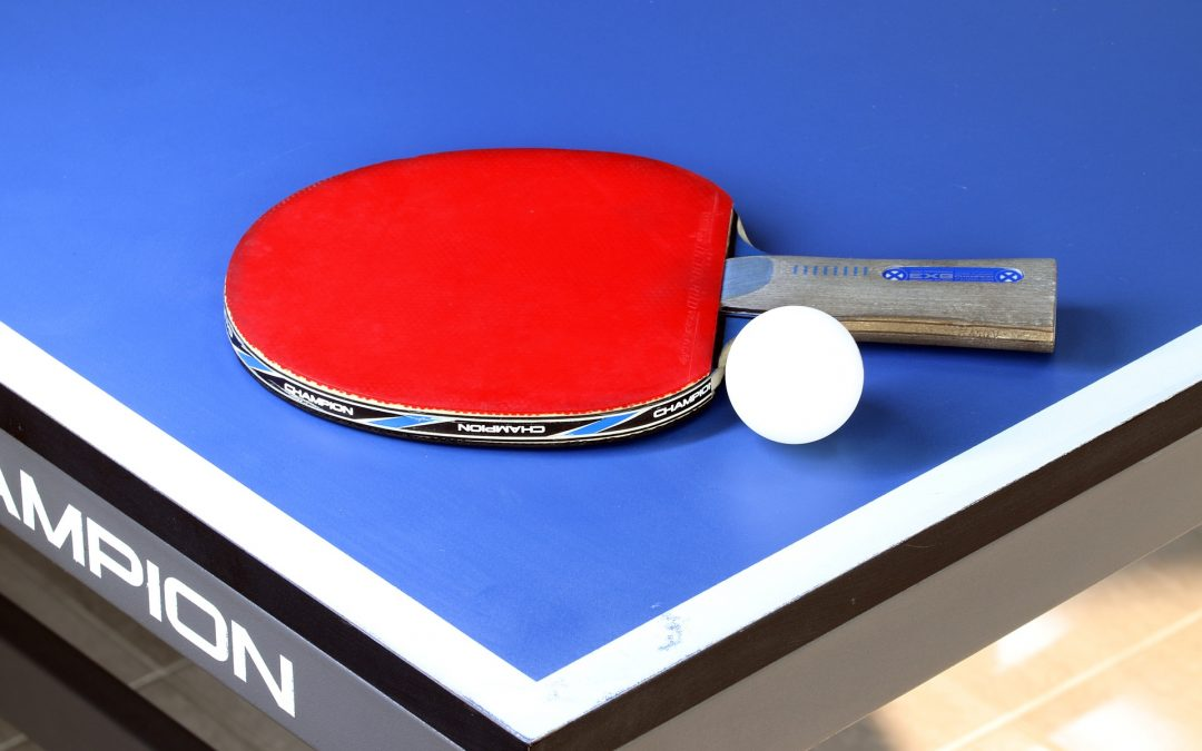 One of the best table tennis rackets, in red, laying on a blue table next to a ping pong ball.